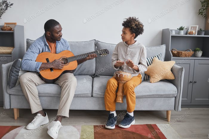 Man And Boy Playing Musical Instruments