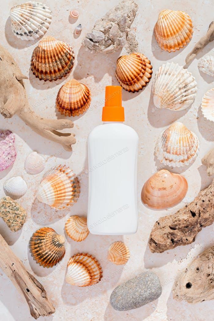 Bottle of sunscreen on background of seashells in hard light
