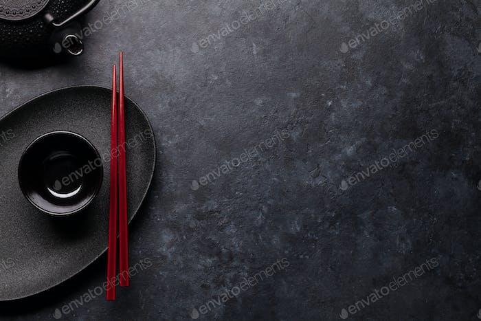 Empty plate, teapot and chopsticks