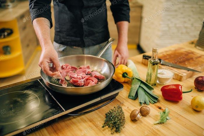 Männliche Person Fleisch mit Kräutern in einer Pfanne kochen