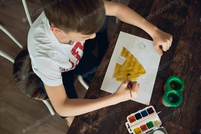 The boy is sitting at the table at home and creatively draws paint.