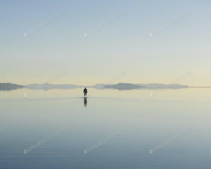 Man walking on vast and flooded Bonneville Salt Flats, Utah