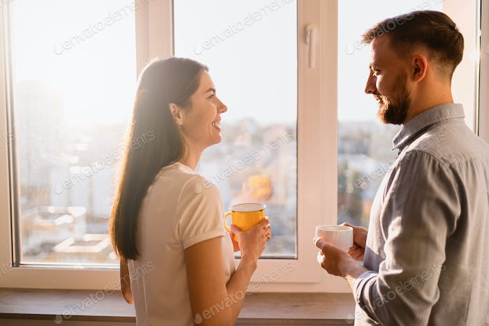 A man and woman drink tea near the window