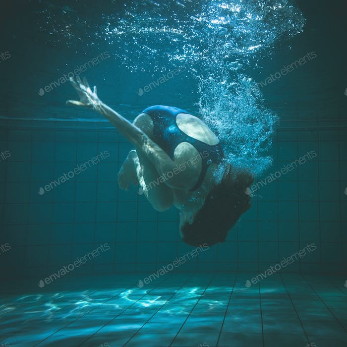 Athletic swimmer doing a somersault underwater in the swimming pool at the leisure centre