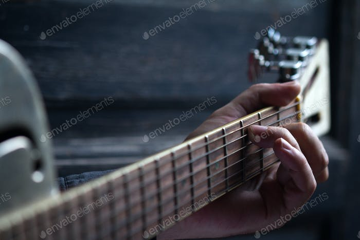 fingers on guitar dark background