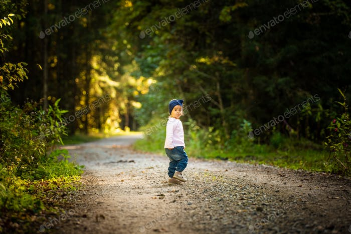 Portrait of 2 years old baby girl in forest walking by herself. Not wanting to follow parents.