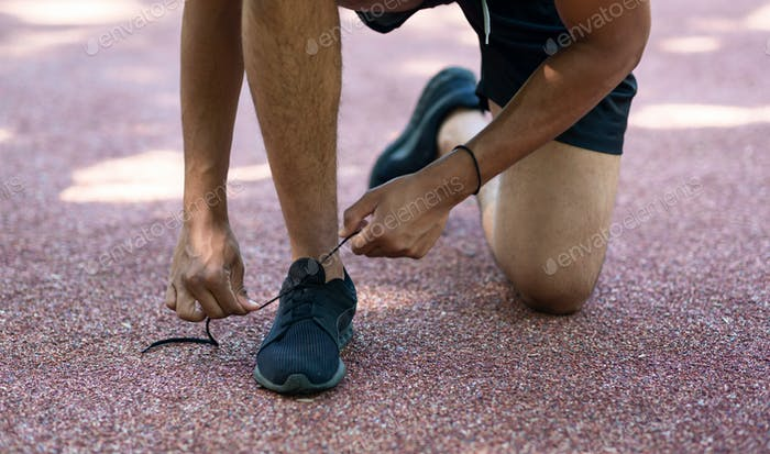 Young sportsman tying shoelaces during his morning run outdoors, close up of legs