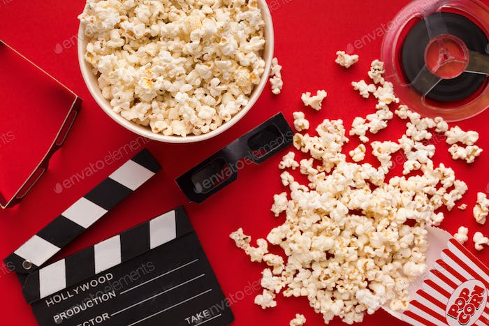 Clapperboard, 3D glasses and popcorn on red background