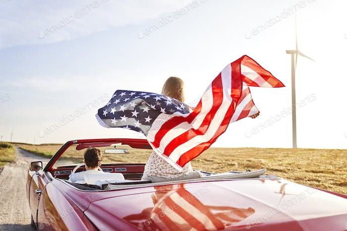 Woman holding an American flag on a road trip