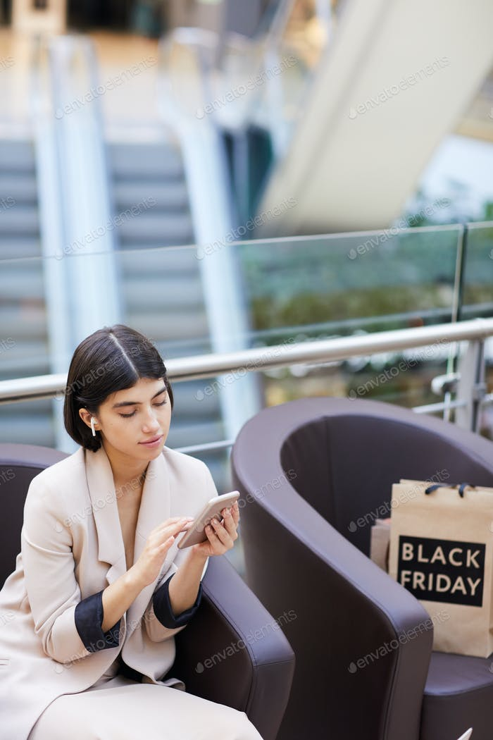 Elegant Woman using Smartphone While Relaxing in Shopping Mall