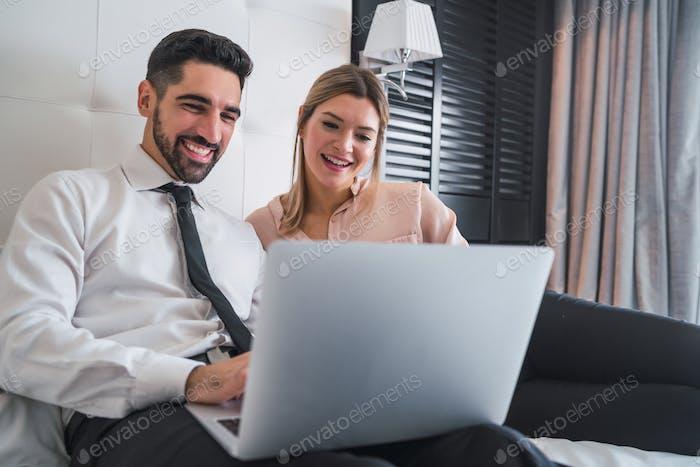 Zwei Geschäftsleute arbeiten zusammen am Laptop.