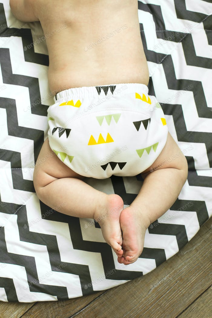 Baby boy in Eco cloth diaper on children's rug. Zero waste, eco-friendly concept. Top view