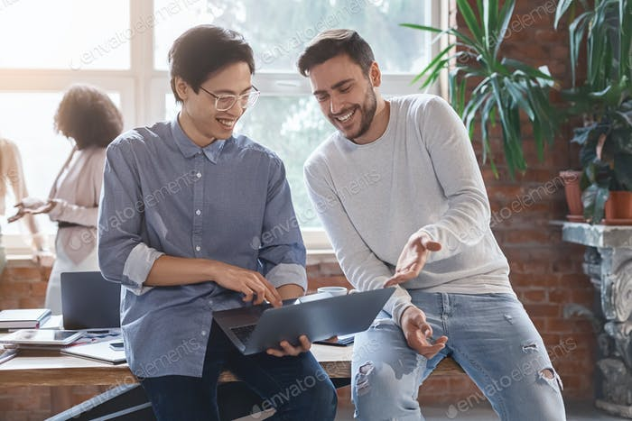 Two guys colleagues sharing creative ideas in casual office atmosphere