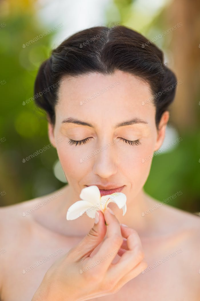 Happy brunette holding a white flower  in a park