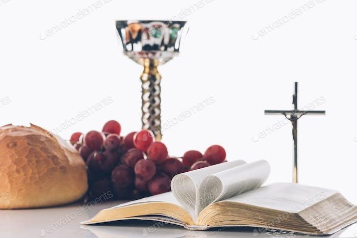 offene Bibel mit christlichem Kreuz und Kelch auf dem Tisch, Heilige Kommunion