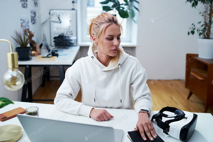 Pretty female freelancer with laptop and virtual reality headset in office