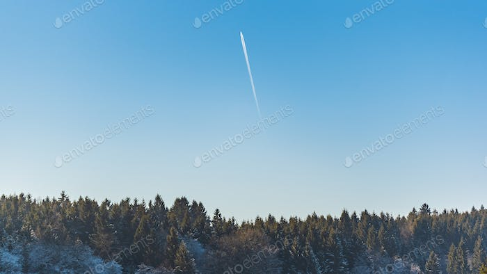 Landscape of forest against blue sky with plane trail on sunny frosty morning
