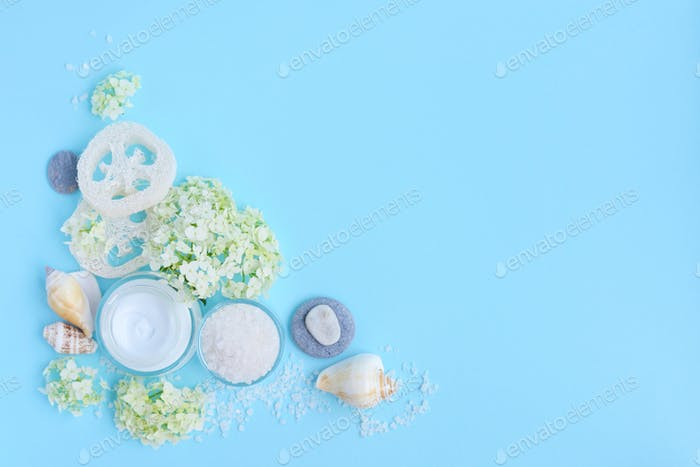Spa composition with cream, salt, shells and flowers on a blue b