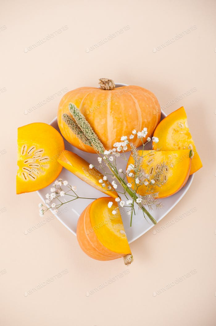 Slices of fresh orange pumpkin and dried flowers on a white plat