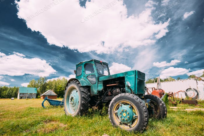 Old Tractor Parking In Backyard In Summer Sunny Day. Special Agr