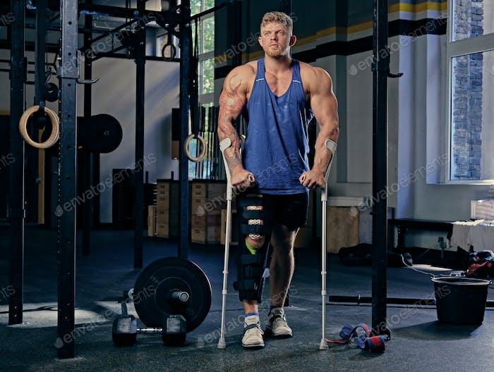 Bodybuilder on crutches in a gym club.