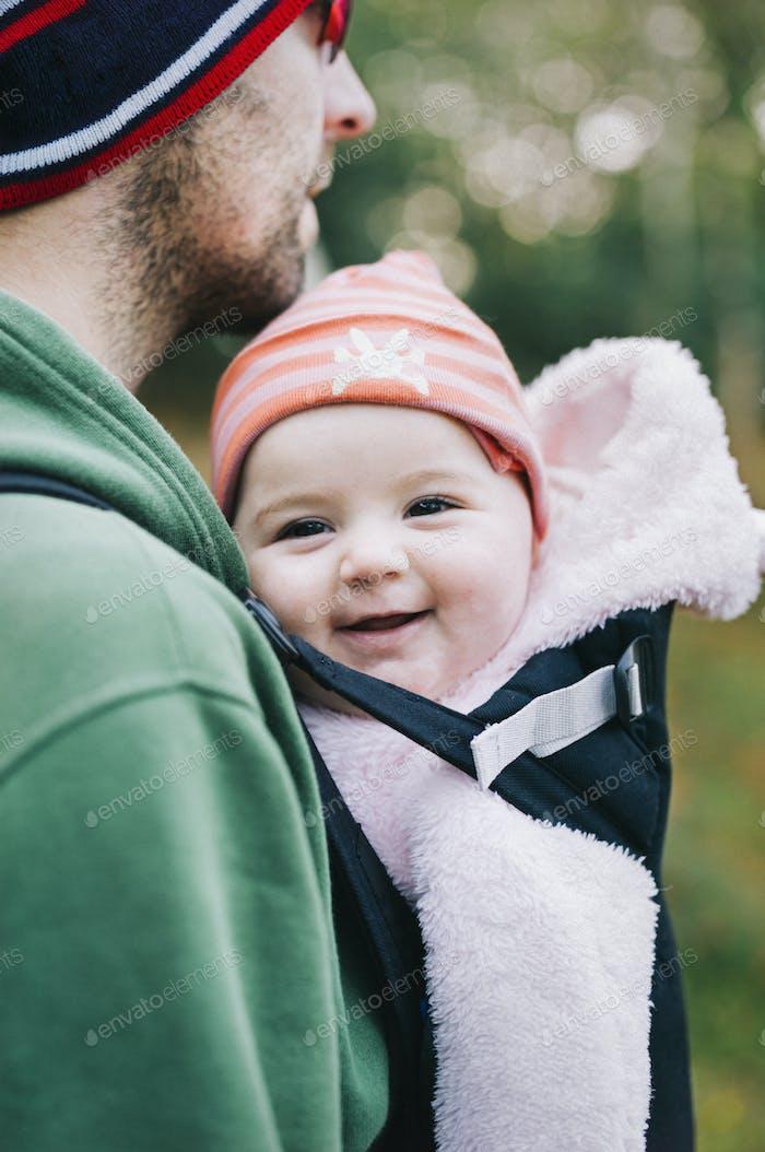 Ein Baby in einer Schlinge, das von ihrem Vater getragen wird, im Winter draußen.