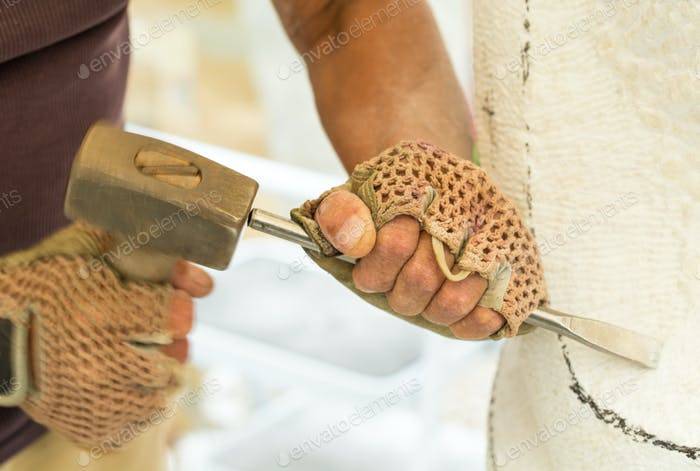 Sculptor hands while working with the tools.