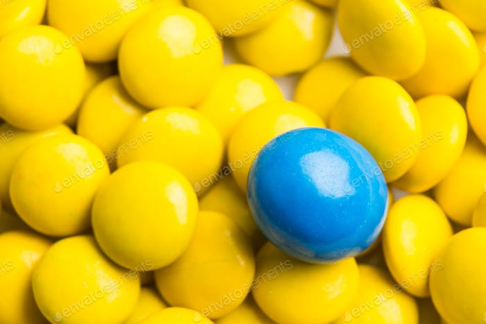 Focus on blue chocolate candy against heaps of yellow candies