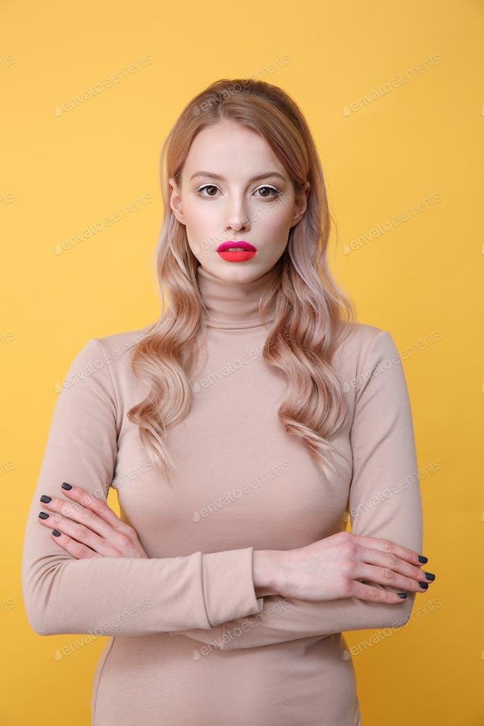 Konzentrierte junge blonde Dame mit hellen Make-up Lippen
