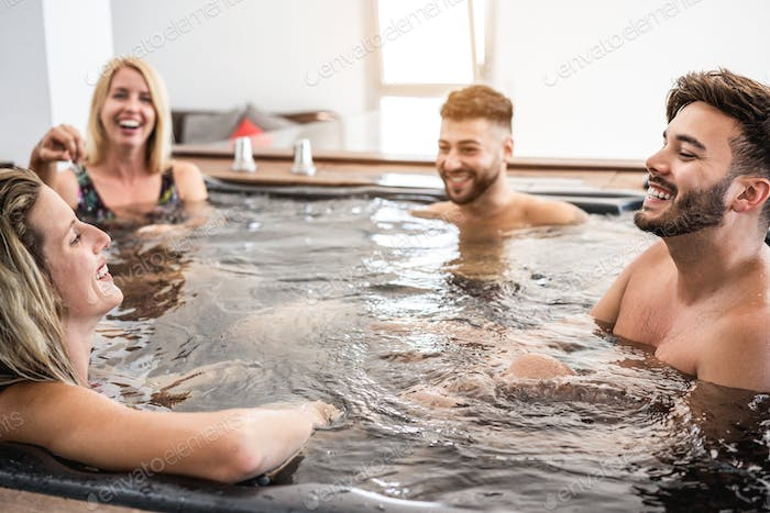 Gruop of friends having fun and relaxing in hot tub indoors at private village party
