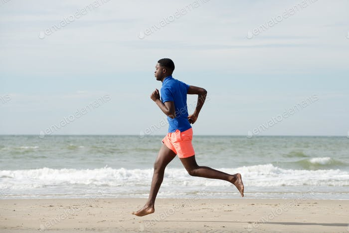 side portrait of healthy african american man running at beach