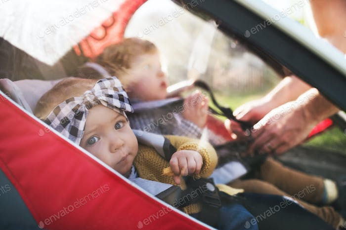 Unrecognizable father with two toddlers in jogging stroller outside in spring nature.