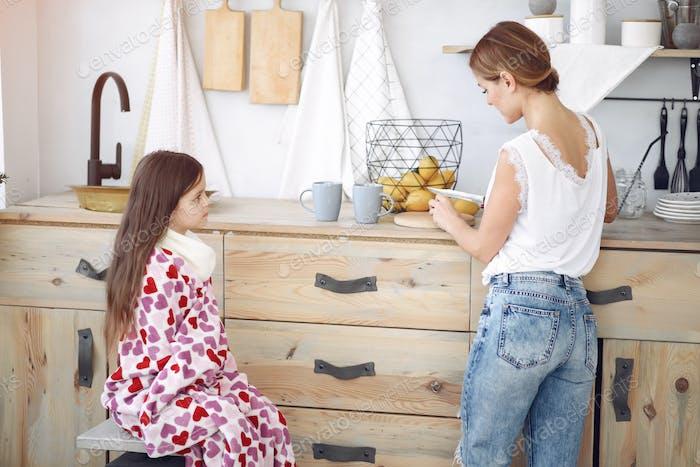 Mutter macht Tee für ihre kranken Tochter