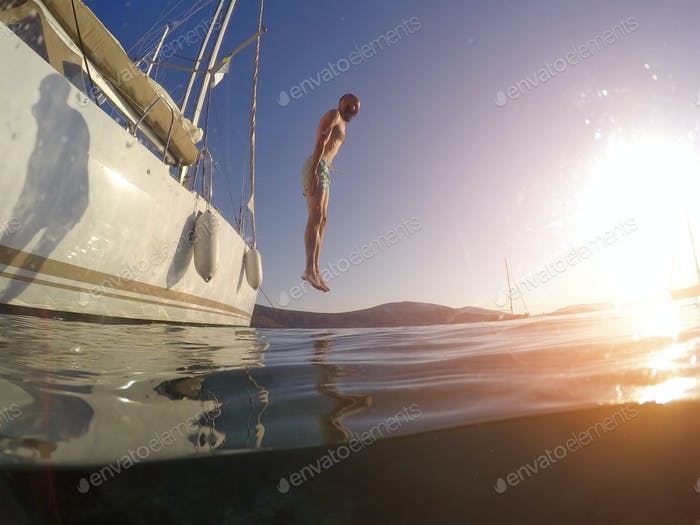 Young man jumping from a yacht into the sea. Underwater photo
