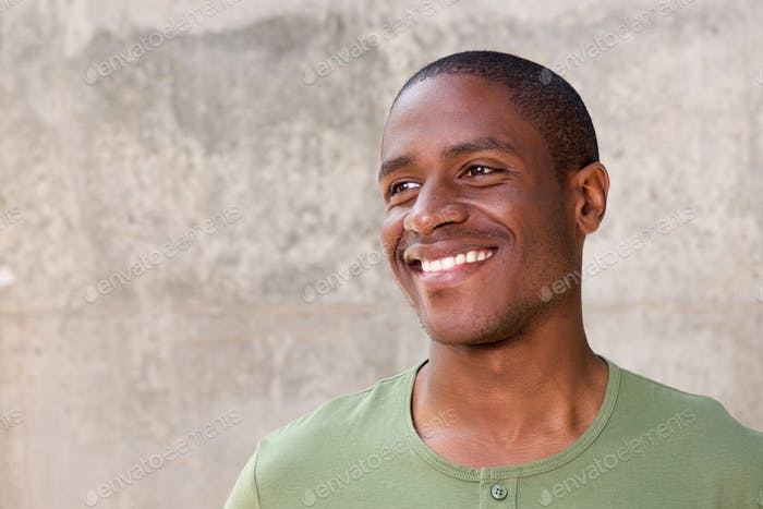 Young african american man on gray background smiling