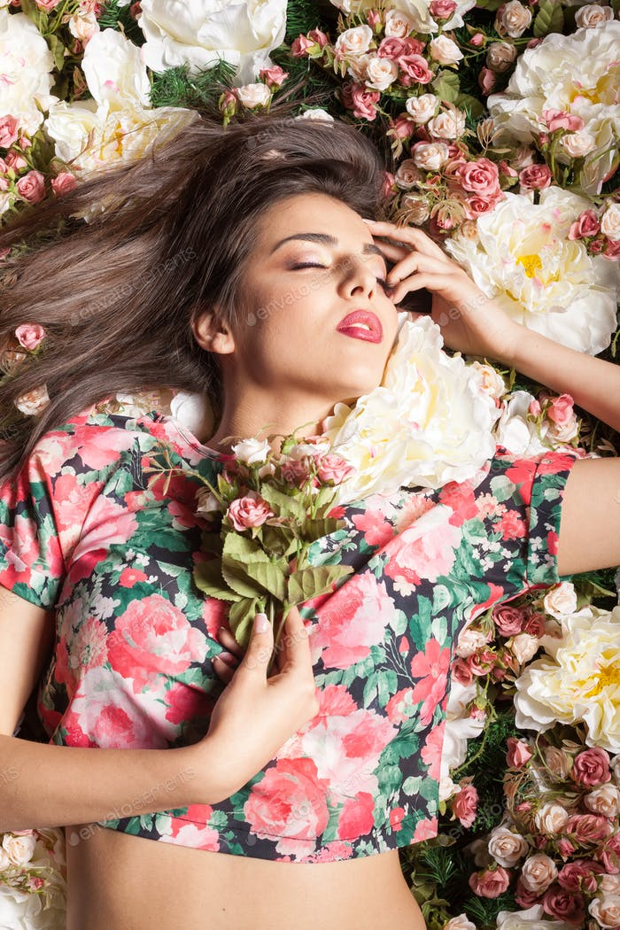 Portrait of gorgeous sensual woman lying down on flowers