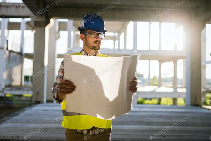 Portrait of male site contractor engineer with hard hat holding blue print paper