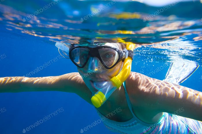 Young women is snorkeling in the tropical water