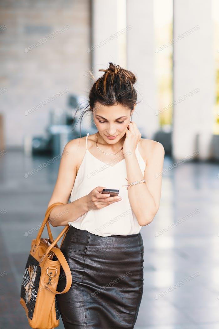 Raffinierte lächelnde Frau zu Fuß und Schreiben oder Lesen von SMS-Nachricht
