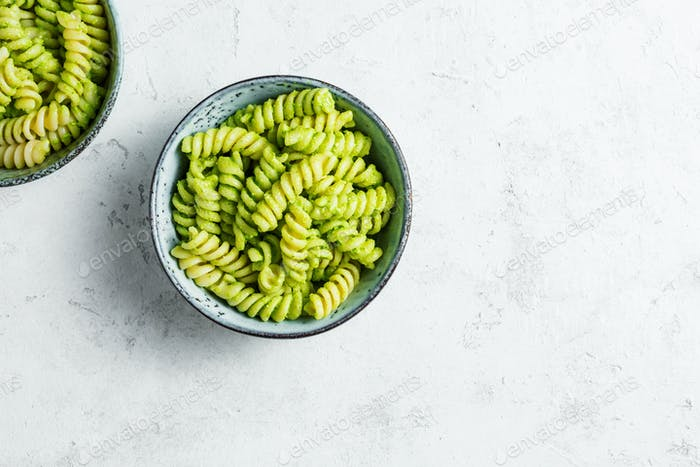 Fusilli pasta with green pesto in bowls on a light background, top view
