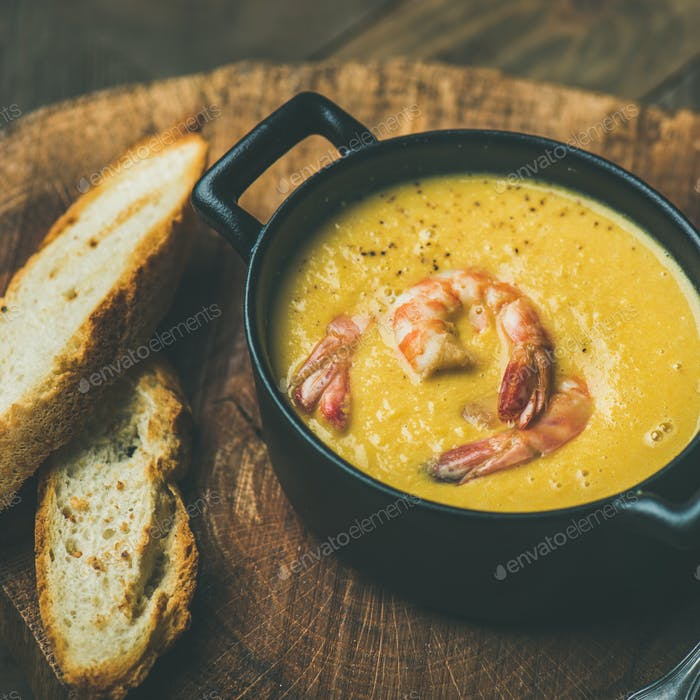 Winter Corn creamy soup with shrimps in pot, square crop