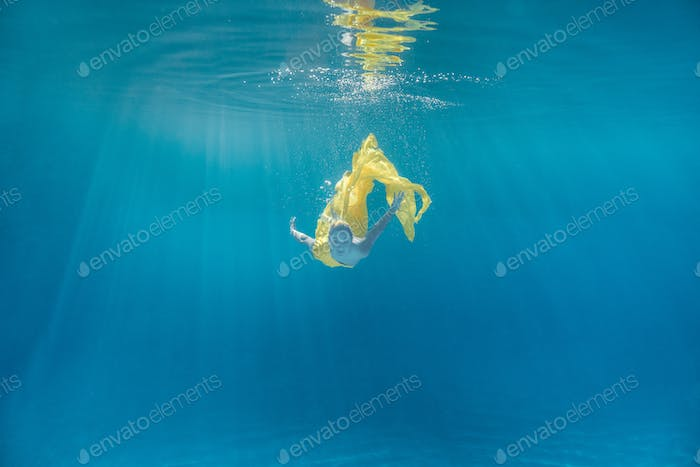 Underwater Picture of Young Woman in Dress Swimming in Swimming Pool