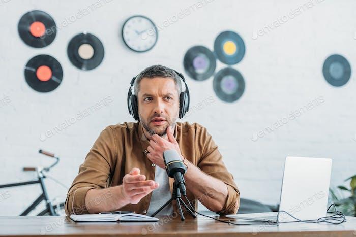 thoughtful radio host in headphones recording podcast in broadcasting studio