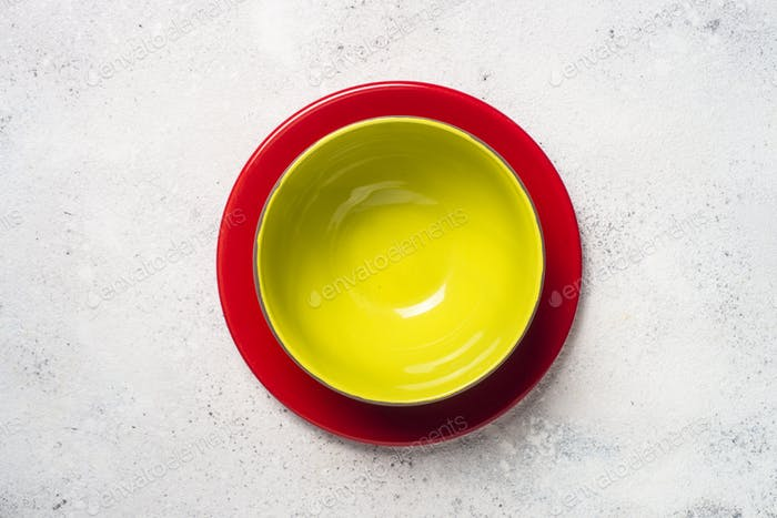 Colored dinnerware - red and green plates on light stone table.