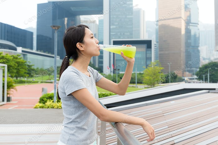 Sport Woman drink with vegetable beverage at outdoor