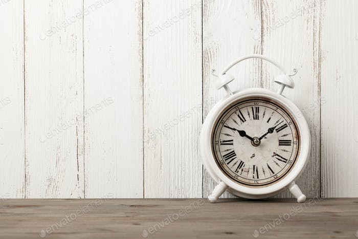 Vintage alarm clock on wooden table