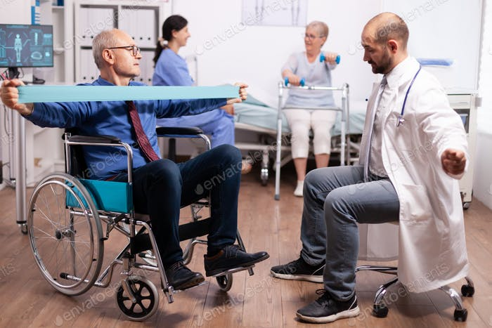 Disabled senior man being assisted by physical therapist