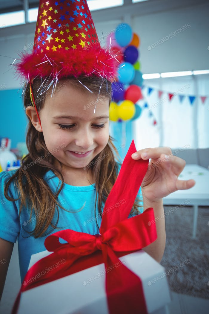 Smiling girl holding a present at the birthday party