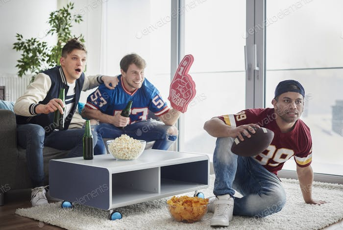 American football fans in front of tv