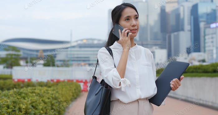 Businesswoman talk to cellphone with laptop computer
